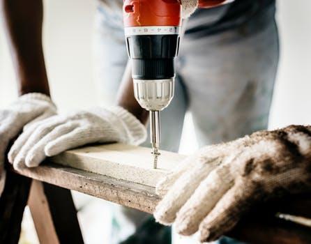 Un homme perce un trou dans une planche en bois