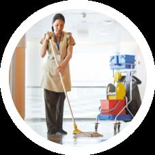 Femme avec le chariot avec les produits de nettoyage